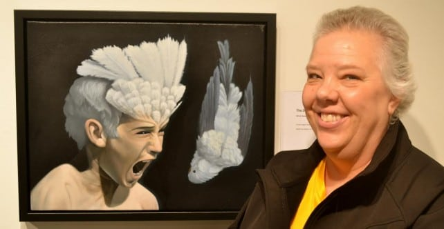 "Woman smiling in front of ""Death of a Budgie-Sattva"""