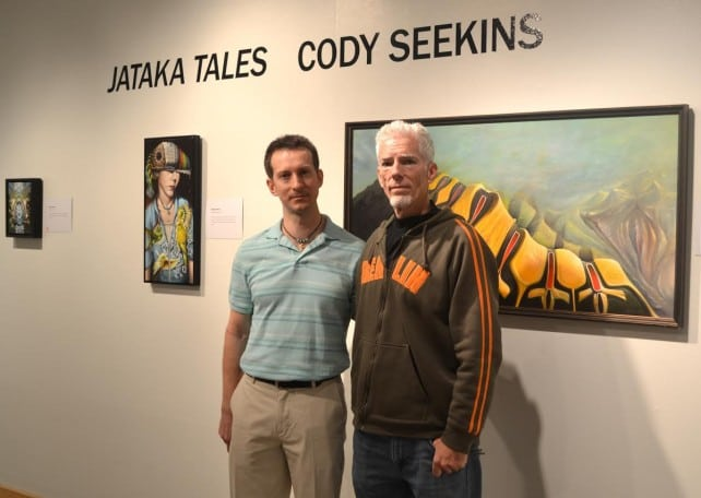 Cody Seekins standing with Christopher Gulick among Cody's paintings