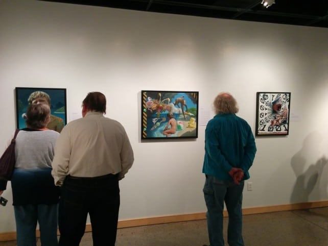 Attendees viewing Cody's paintings.