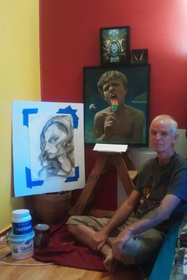Stephan sitting with his newest Seekins' artworks at his residence.