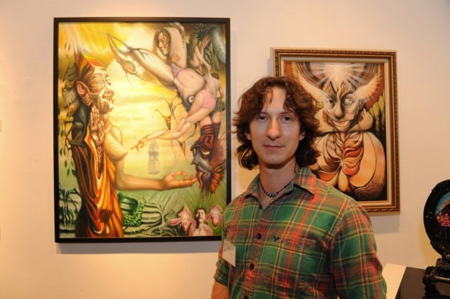 Cody smiling with his paintings.