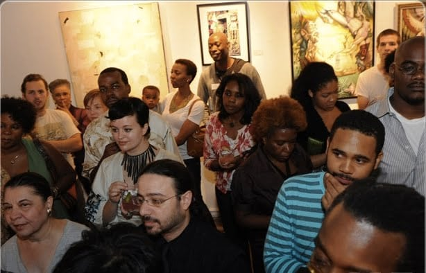 A crowd of people viewing artworks at the show.